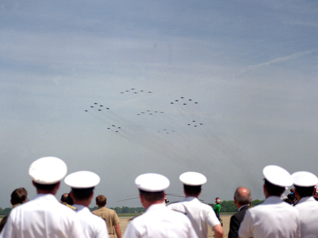 Navy officers watch a flyover comprised of Carrier Air Wing 1 (CVW-1) aircraft from Attack Squadron 85 (VA-85), Fighter Squadron 33 (VF-33) and Fighter Squadron 102 (VF-102). The wing is returning from the Persian Gulf area where it was deployed aboard the aircraft carrier USS AMERICA (CV-66) while deployed in the Persian Gulf area during Operations Desert Shield/Desert Storm