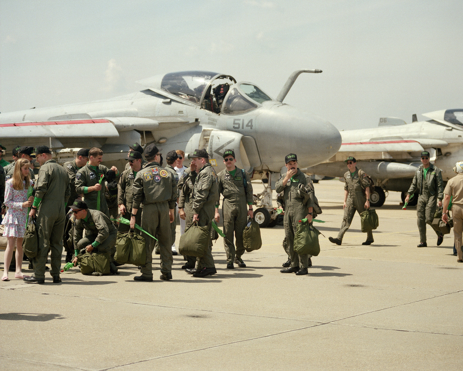 Pilots from Carrier Air Wing 1 (CVW-1) walk past an Attack Squadron 85 (VA-85) A-6E Intruder aircraft on the flight line after returning home from deployment in the Persian Gulf area. CVW-1 was stationed aboard the aircraft carrier USS AMERICA (CV 66) while serving during Operations DESERT SHIELD/DESERT STORM