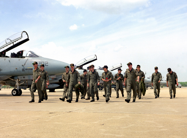 Pilots of Fighter Squadron 33 (VF-33) walk in front of their F-14A Tomcat aircraft following their arrival along with other squadrons of Carrier Air Wing 1 (CVW-1). The wing has been deployed in the Persian Gulf area aboard the aircraft carrier USS AMERICA (CV-66) during Operations Desert Shield/Desert Storm