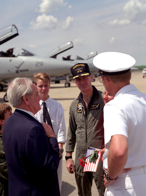 Robert Fentess, vice mayor of Virginia Beach, left, and Rear Adm. Paul W. Parcells, deputy assistant secretary of defense, Atomic Energy, greet CMDR. Tony Reade, executive officer of Fighter Squadron 33 (VF-33), following the squadron's arrival at the station. VF-33 has returned from the Persian Gulf area, along with other squadrons of Carrier Air Wing 1 (CVW-1), following deployment aboard the aircraft carrier USS AMERICA (CV-66) during Operations Desert Shield/Desert Storm