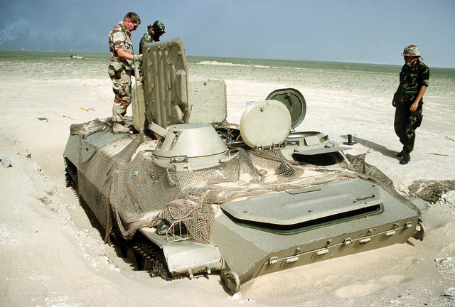 U.S. soldiers inspect an Iraqi MT-LB armored personnel carrier abandoned near Ali Al Salem Air Base during Operation Desert Storm.