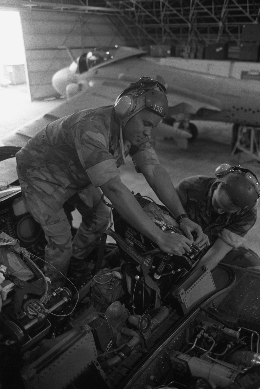 GYSGT Vince Jones and LCPL Carl A. Forester install an ejection seat in a Marine Attack Squadron 332 (VMA-332) A-6E Intruder aircraft
