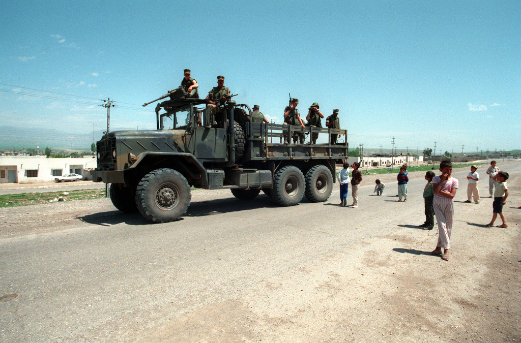 Children come out to see members of Marine Service Support Group 24 (MSSG-24) arrive in an M-934 5-ton cargo truck, part of a convoy entering Zakhu. The Marines will be assisting the inhabitants of a tent city set up as part of Operation Provide Comfort, an Alled effort to aid Kurdish refugees who fled the forces of Saddam Hussein in northern Iraq.