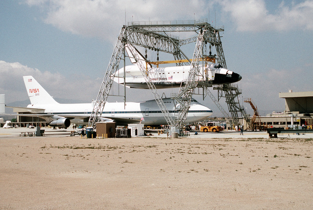 The NASA 747 Shuttle Carrier Aircraft (SCA) is pulled into position beneath the Space Shuttle Endeavour OV-105 (Orbiter Vehicle-105), that is suspended beneath a massive lifting structure at Rockwell International's Air Force Plant 42, Site 1, at Palmdale. Exact Date Shot Unknown