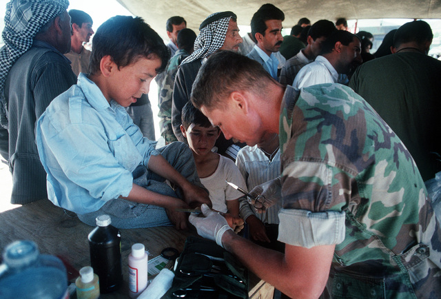 CHIEF Hospital Corpsman Arthur Angel treats a young Kurdish refugee's blistered foot in a medical clinic on the outskirts of the city. The Marines and sailors of Marine Expeditionary Unit (MEU) Service Support Group 24 (MSSG-24) set up the clinic and a water purification station for the Kurdish refugees as part of Operation Provide Comfort