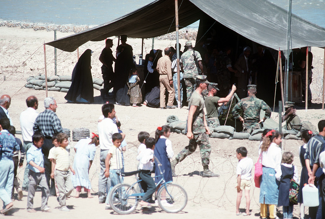Kurdish refugees gather outside a medical clinic and water purification station set up on the outskirts of the city by Marine Expeditionary Unit (MEU) Service Support Group 24 (MSSG-24) as part of Operation Provide Comfort