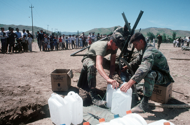 LCPL Joseph Williams, left, and CPL Thomas Quinn fill a jug with clean water at a medical clinic and water purification station on the outskirts of the city as Kurdish refugees wait outside the compound's fence. The Marines are members of Marine Expeditionary Unit (MEU) Service Support Group 24 (MSSG-24), which is providing services to the refugees as part of Operation Provide Comfort