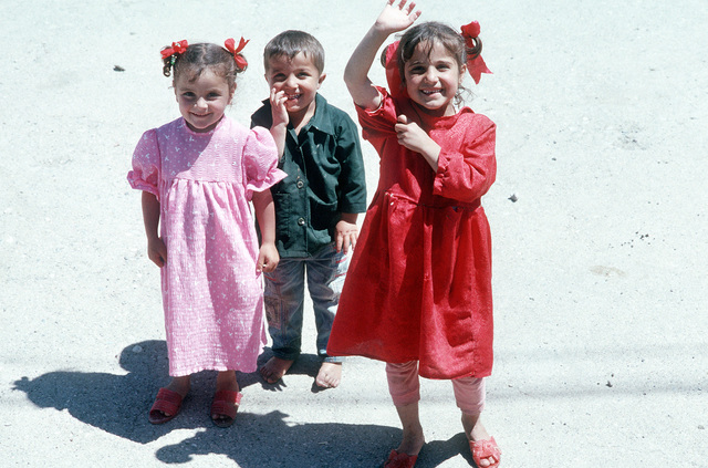 Three Iraqi children stand on the side of a road to greet passing American servicemen. Marines of the 24th Marine Expeditionary Unit (24th MEU) and MEU Service Support Group 24 (MSSG-24) are furnishing aid to the Kurdish refugees in the Zakhu area as part of Operation Provide Comfort
