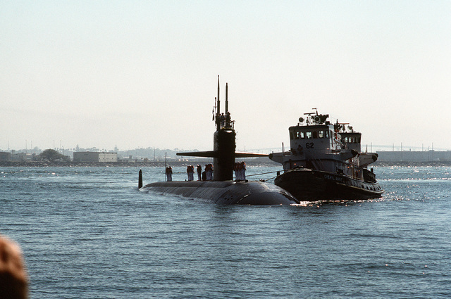 A commercial tug pushes the nuclear-powered attack submarine USS LOUISVILLE (SSN-724) toward the pier following its deployment to the Persian Gulf region for Operation Desert Shield and Operation Desert Storm. During Operation Desert Storm, the LOUISVILLE became the first submarine to launch a Tomahawk land attack missile in a wartime situation