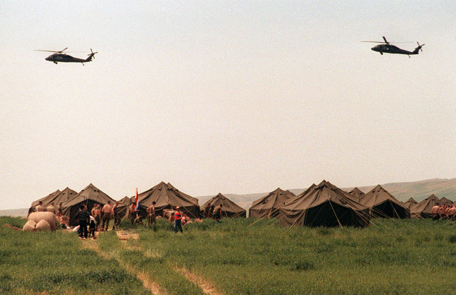 U.S. Army UH-60 Black Hawk helicopters patrol over a Marine camp near Zakhu. The Marines assisted in setting up a nearby tent city on the Turkey-Iraq border as part of Operation Provide Comfort, an Allied effort to aid Kurdish refugees who fled from the forces of Saddam Hussein in northern Iraq
