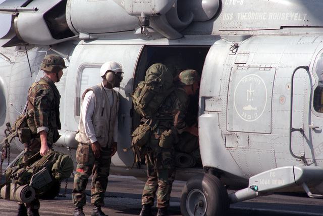 Members of the Special Purpose Marine Air Ground Task Force (SPMAGTF) board a Helicopter Anti-submarine Squadron 3 (HS-3) SH-60F Sea Hawk helicopter on the flight deck of the nuclear-powered aircraft carrier USS THEODORE ROOSEVELT (CVN-71). The Marines are going to participate in a training exercise in Italy. The ROOSEVELT is operating in the Adriatic in support of Operation Deny Flight