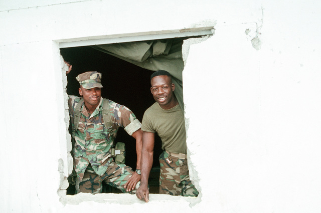 SGT Robert A. Ford, left, and CPL Reginald E. Harper of Headquarters and Service Co., Battalion Landing Team 2nd Bn., 8th Marines (BLT 2/8), 24th Marine Expeditionary Unit (24TH MEU), look out the window of a former Iraq army building during Operation Provide Comfort, a multinational effort to aid the refugees in northern Iraq and southern Turkey