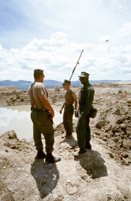 Three Seabees from Naval Mobile Construction Battalion 133 (NMCB-133) discuss plans to drain the water from a bomb crater on the runway at an Iraqi airfield. The airfield, which had been under construction prior to the start of the Persian Gulf war, is being repaired to allow relief supplies to be flown in for nearby Kurdish refugees as part of Operation Provide Comfort