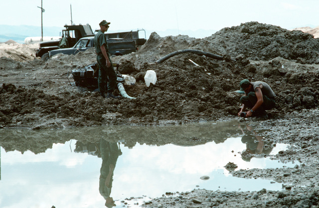 Two Seabees from Naval Mobile Construction Battalion 133 (NMCB-133) set up a pump to drain water from a bomb crater on the runway at an Iraqi airfield. The airfield, which had been under construction prior to the start of the Persian Gulf war, is being repaired to allow relief supplies to be flown in for nearby Kurdish refugees as part of Operation Provide Comfort