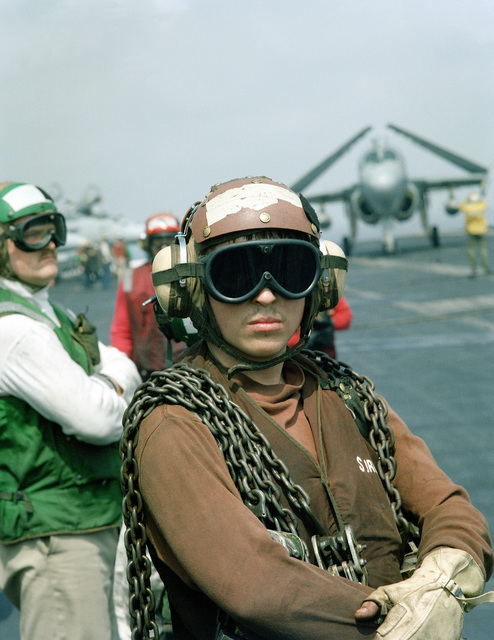 With tie-down chains draped over his shoulders, a plane captain waits for his aircraft to be recovered aboard the nuclear-powered aircraft carrier USS THEODORE ROOSEVELT (CVN-71). The ROOSEVELT is on station in the eastern Mediterranean to support Operation Provide Comfort, a multinational effort to aid Kurdish refugees in southern Turkey and northern Iraq.