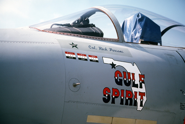 A close-up view of the artwork on the side of a 33rd Tactical Fighter Wing F-15C Eagle aircraft on display at the 1991 Department of Defense Joint Services Open House. The small flags painted beside the artwork represent the three Iraqi aircraft shot down by the aircraft's pilot, COL. Rick Parsons, during Operation Desert Storm