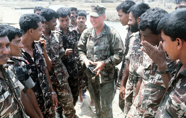 CPL Robert Cutler, 5th Marines, explains the entrenching tool (E-tool) to Bangladesh soldiers. Marines are in the region as part of Operation Sea Angel, a U.S. military effort to aid victims of a cyclone which struck the area on April 30th