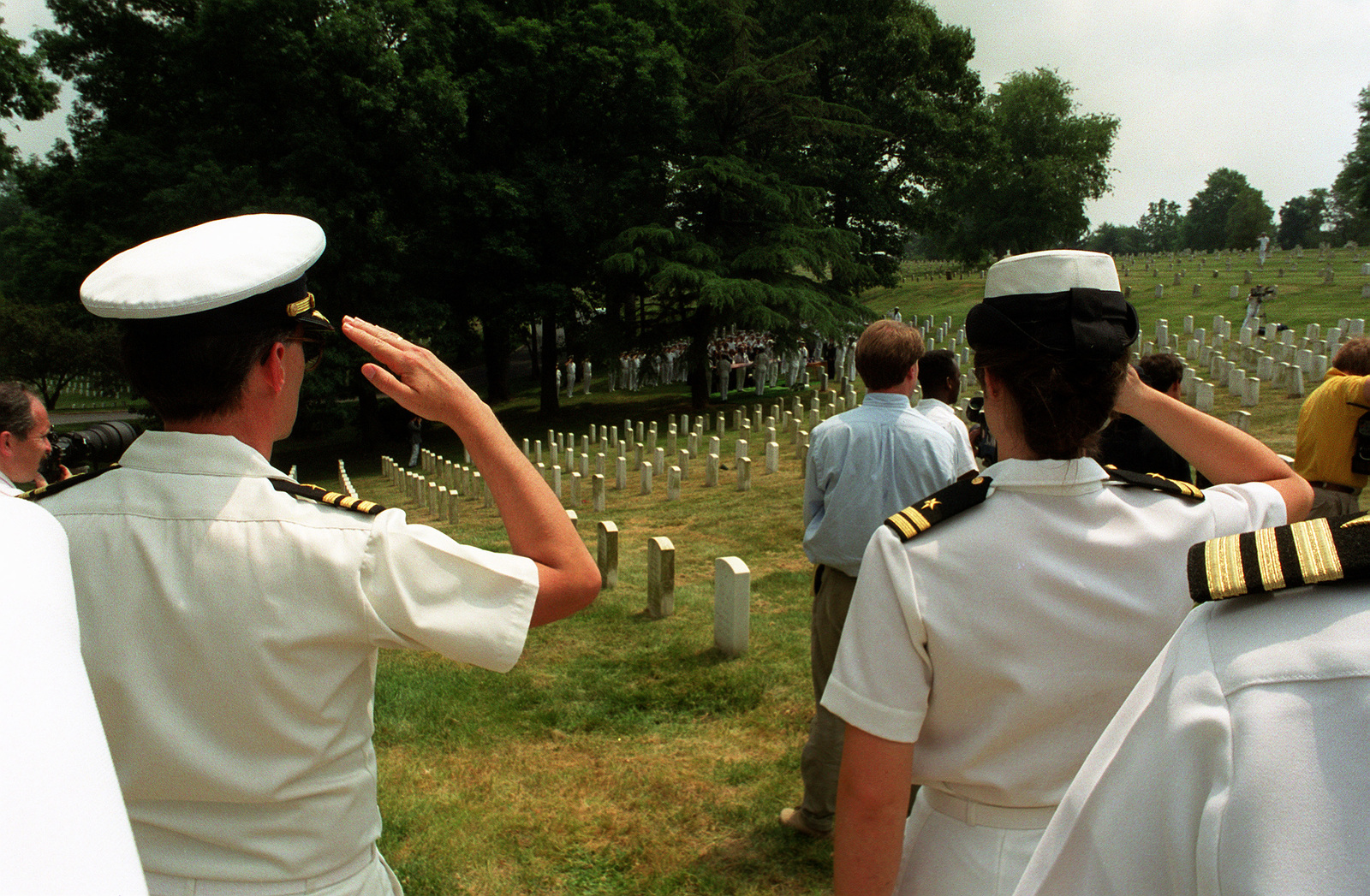 Two Navy officers salute during a memorial service at Arlington National Cemetery for LT. CMDR. Barry T. Cooke of Attack Squadron 36 (VA-36). Cooke and his bombardier/navigator, LT. Patrick K. Connor, were killed when their A-6E Intruder aircraft was shot down on February 2, 1991, during Operation Desert Storm
