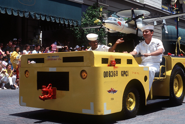 """A sailor drives an MD-3A tow tractor with a model E-2C Hawkeye aircraft attached along the parade route during the """"San Diego Salutes the Troops"""" parade. The parade is being held in honor of all veterans, with special recognition being given to units that took part in Operation Desert Shield and Operation Desert Storm"""