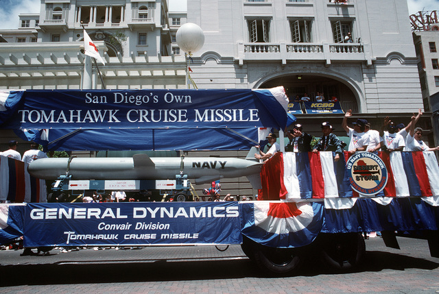 """Representatives of the General Dynamics Corp. ride on a trailer with a BGM-109 Tomahawk cruise missile during the """"San Diego Salutes the Troops"""" parade. The parade is being held to honor all veterans, with special recognition being given to units that took part in Operation Desert Shield and Operation Desert Storm"""