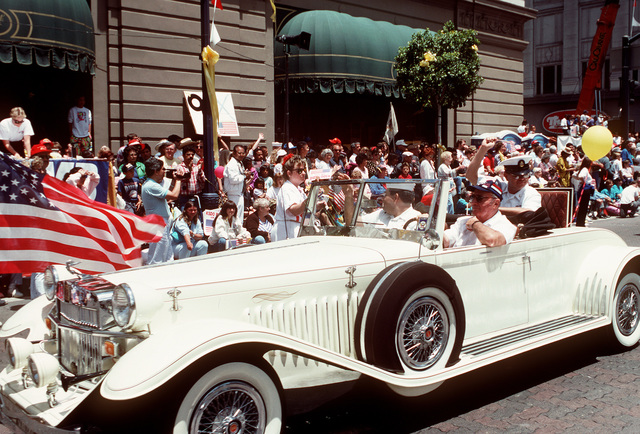 "Two sailors ride in an antique automobile during the ""San Diego Salutes the Troops"" parade. The parade is being held in honor of all veterans, with special recognition being given to units that took part in Operation Desert Shield and Operation Desert Storm"