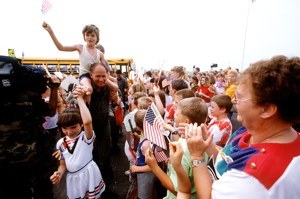 Nichole Doehring leads MAJ. Skip Davenport through the crowd as he and other members of the 8th Special Operations Squadron are welcomed upon their arrival. The servicemen corresponded with the children while stationed in the Persian Gulf area during Operations Desert Shield/Desert Storm. Now that they have returned from deployment, the men have traveled to Illinois to meet and spend a day with their pen pals