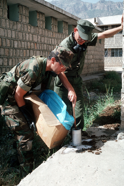 Members of a preventive medicine team mix an insecticide to fight mosquitoes and other insects in a refugee camp during Operation Provide Comfort, an Allied effort to aid Kurdish refugees who fled the forces of Saddam Hussein in northern Iraq. The team is inspecting camps for unsanitary conditions which might promote disease