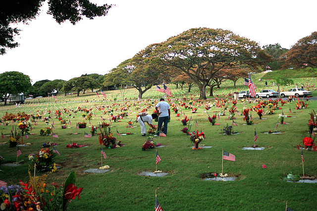 Two visitors place flowers on a grave at the National Memorial Cemetery of the Pacific, also known as the Punchbowl, in observance of Memorial Day. A flag and a flower lei have been placed on each grave in the cemetery by area Boy Scouts.