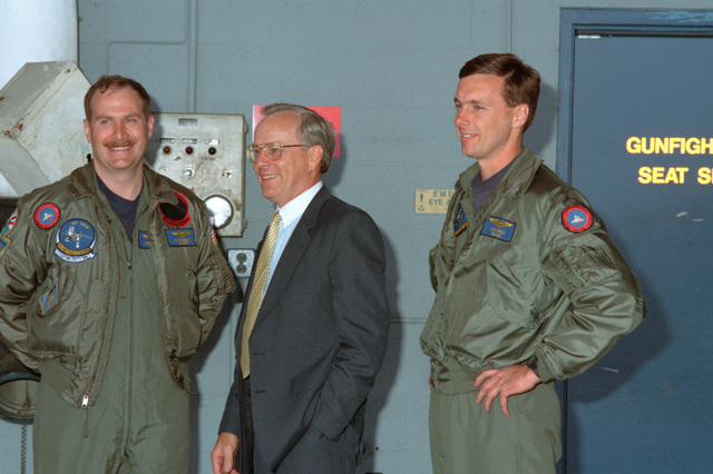 "US Navy (USN) Secretary of the Navy (SECNAV) Honorable H. Lawrence Garrett visits with aircrew personnel, Lieutenant Commander (LCDR) Mike ""Sluggo"" Higgins (left), USN and Lieutenant (LT) Clay ""Snooze"" Snaza, USN, from the Fighter Squadron 124 (VF-124), Gunfighters, Naval Air Station (NAS) Miramar"
