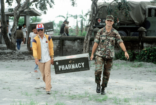 A Filipino man helps LTC James Baker, commander of the 3rd Tactical Fighter Wing's civic action program, carry a box of medical supplies into the Santa Rosa School. The school is being used as a clinic for more than 1,300 evacuees who have fled the mudslides and flooding caused by heavy rains that fell following the eruption of Mount Pinatubo
