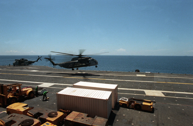 A Marine Heavy Helicopter Squadron 772 (HMH-772) CH-53 Sea Stallion helicopter lifts off from the flight deck of the aircraft carrier USS MIDWAY (CV 41). The helicopter is transporting evacuees from Clark Air Base and Naval Station, Subic Bay, who are being evacuating from the area in the aftermath of the eruption of Mount Pinatubo, a volcano that came alive on June 10th for the first time in over 600 years.