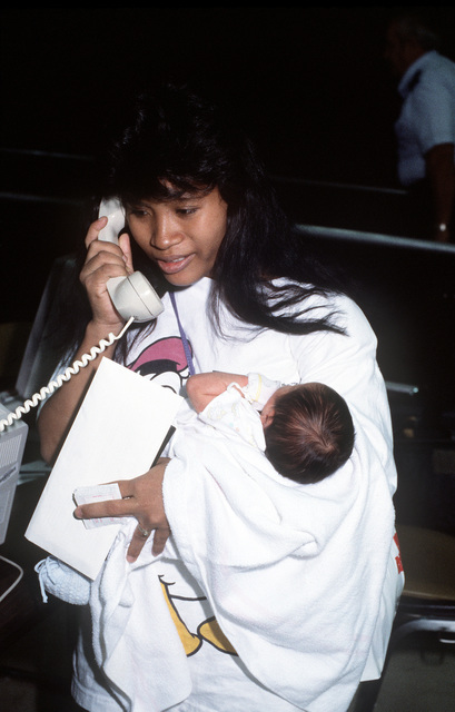 A military dependent makes a phone call after arriving on base following an evacuation flight from the Philippines. The woman is one of over 20,000 evacuees removed from the area during Operation Fiery Vigil in the aftermath of Mount Pinatubo's eruption. The volcano erupted for the first time in over 600 years, causing disruption of operations at both Clark Air Force Base and Naval Station, Subic Bay