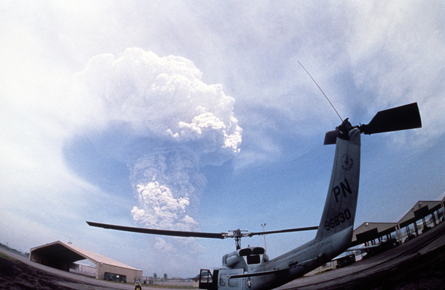 A mushroom cloud of ash from Mount Pinatubo billows in the background as a UH-1N Iroquois helicopter from the 3rd Tactical Fighter Wing is readied for takeoff during evacuation. More than 20,000 evacuees have been removed from the area as a part of the U.S. military's Operation Fiery Vigil after more than four inches of fallen ash disrupted base operations