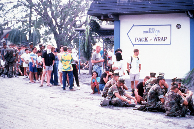 Civilian and military personnel line up for processing during evacuation from the area following the eruption of Mount Pinatubo. More than 20,000 evacuees have been removed as a part of the U.S. military's Operation Fiery Vigil after more than four inches of fallen ash disrupted base operations