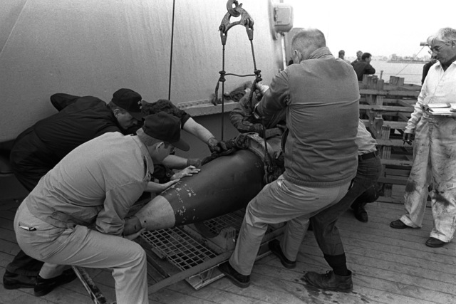 Crewmen position a 16-inch projectile on a pallet on the battleship USS MISSOURI (BB-63). Ammunition is being offloaded after the ship's return from the Persian Gulf following the cease-fire that ended Operation Desert Storm