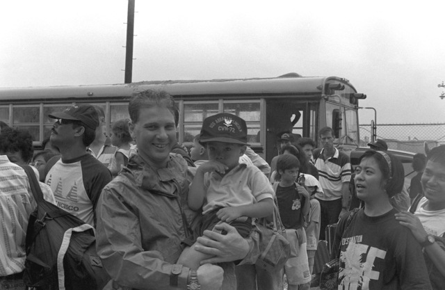 Dependents of U.S. military personnel prepare to board the nuclear-powered aircraft carrier USS ABRAHAM LINCOLN (CVN 72) during evacuation of Clark Air Base and Naval Station, Subic Bay. Evacuees are being transported from the area in the aftermath of the eruption of Mount Pinatubo, a volcano that came alive on June 10th for the first time in over 600 years