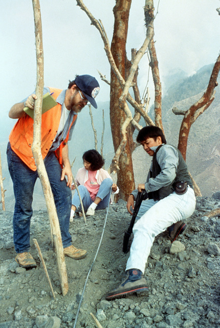 Dr. Christopher Newhall of the U.S. Geological Survey joins Art Daag and Bellia Tubianosa of the Philippine Institute of Volcanology and Seismology as the three gather rock and soil samples from Mount Pinatubo in the aftermath of its eruption. The volcano, which came alive for the first time in over 600 years, forced the U.S. military to conduct Operation Fiery Vigil evacuation efforts during which over 20,000 evacuees will be removed from Clark Air Base, foreground, and Naval Station, Subic Bay