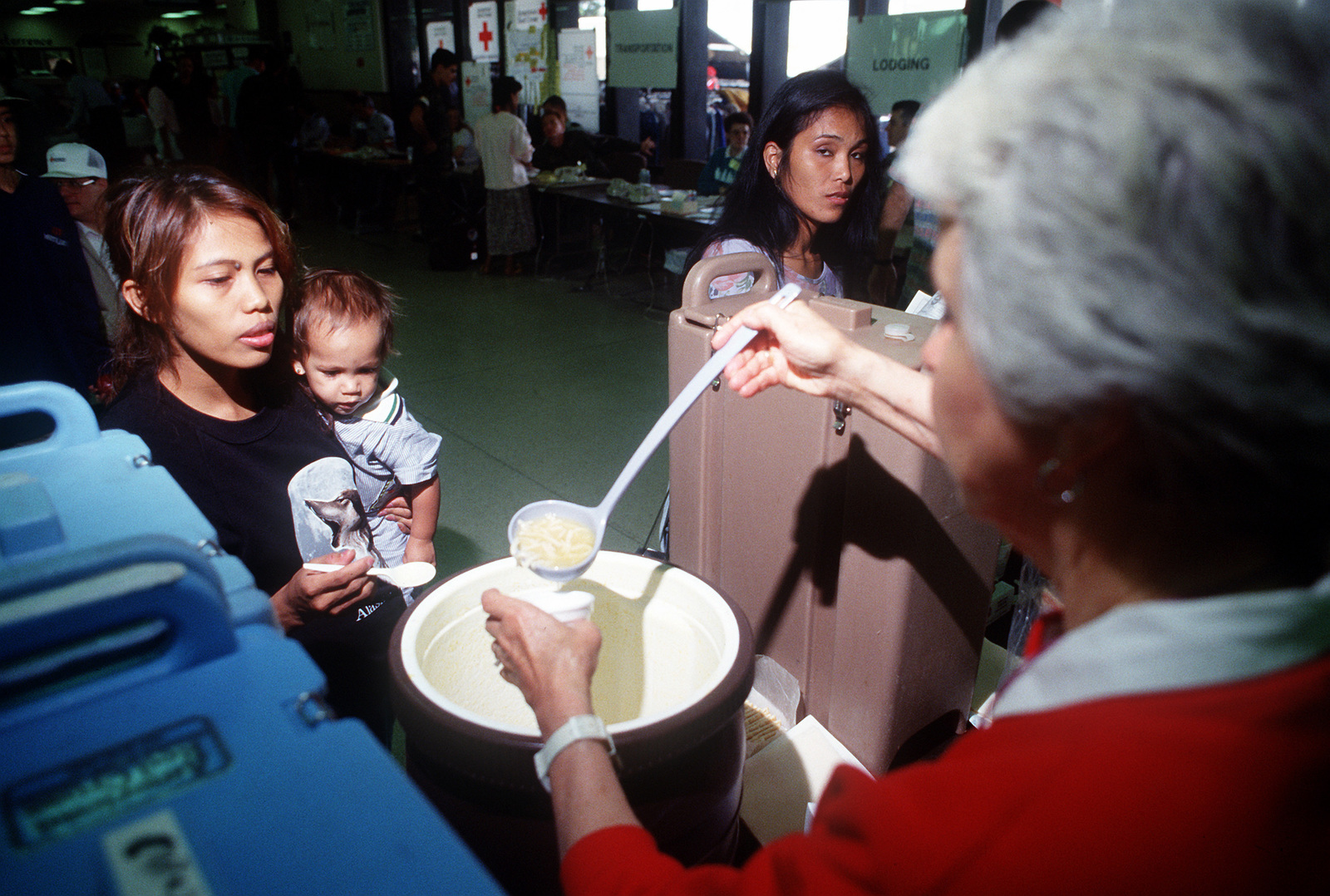 Erlinda Gale, wife of an airman at Clark Air Base, Philippines, receives a bowl of soup from a volunteer at the Military Airlift Command terminal during Operation Fiery Vigil. McChord is a stopover for hundreds of U.S. Air Force and Navy personnel, civilian employees and their dependents being evacuated from the Philippines after fallen ash from the erruption of Mount Pinatubo collapsed buildings and disrupted operations on military bases.