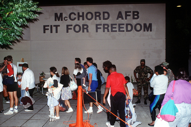 Evacuees enter the base fitness center, where they will continue being processed during Operation Fiery Vigil. McChord is a stopover for hundreds of U.S. Air Force and Navy personnel, civilian employees and their dependents being evacuated from the Philippines after fallen ash from the erruption of Mount Pinatubo collapsed buildings and disrupted operations on military bases.