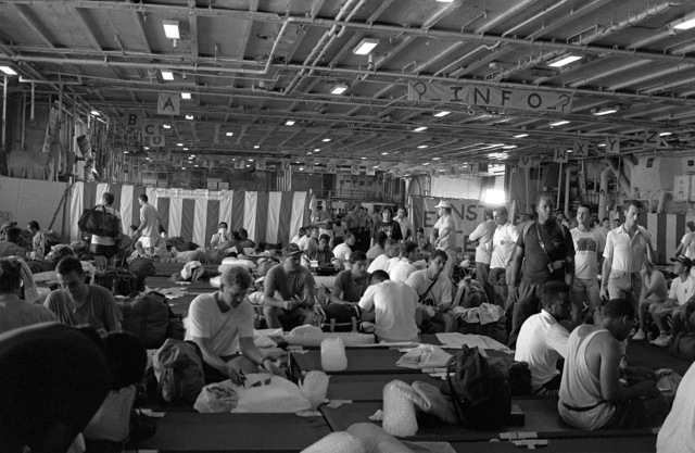 Evacuees from Clark Air Base and Naval Station, Subic Bay settle into their temporary quarters aboard the aircraft carrier USS MIDWAY (CV 41). Military personnel and dependents are being transported from the area in the aftermath of the eruption of Mount Pinatubo, a volcano that came alive on June 10th for the first time in over 600 years