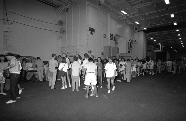 Evacuees from Clark Air Base and Naval Station, Subic Bay stand in line to have records processed aboard the nuclear-powered aircraft carrier USS ABRAHAM LINCOLN (CVN 72). Military personnel and dependents are being transported from the area in the aftermath of the eruption of Mount Pinatubo, a volcano that came alive on June 10th for the first time in over 600 years