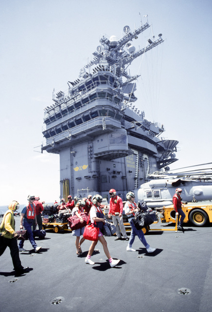 Families walk across the flight deck of the nuclear-powered aircraft carrier USS ABRAHAM LINCOLN (CVN-72) to board a helicopter as the ship steams to the Philippines island of Cebu during Operation Fiery Vigil. The families were evacuated from Clark Air Base and Naval Station, Subic Bay, Philippines, after volcanic ash from the eruption of Mount Pinatubo covered the two bases and disrupted services