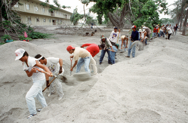 Filipino workers clear volcanic ash from a drainage ditch in anticipation of the upcoming rainy season. The ash was deposited during the eruption of Mount Pinatubo