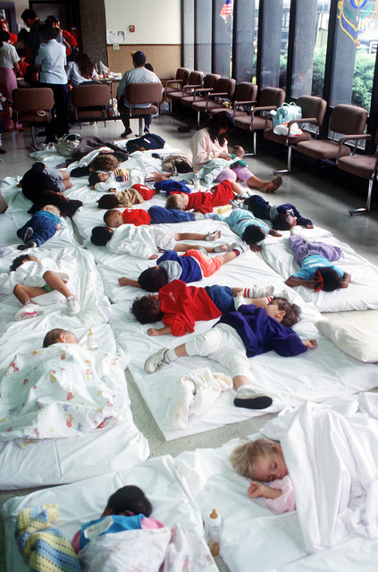 Infants and toddlers sleep in a makeshift nursery at the Military Airlift Command terminal during Operation Fiery Vigil. McChord is a stopover for hundreds of U.S. Air Force and Navy personnel, civilian employees and their dependents being evacuated from the Philippines after fallen ash from the eruption of Mount Pinatubo collapsed buildings and disrupted operations on military bases.