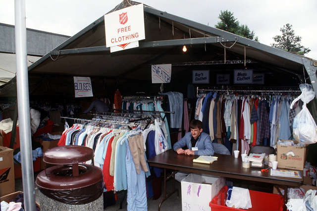 Leroy Neva, a volunteer from Tacoma, Wash, mans the Salvation Army's free clothing distribution booth outside the Military Airlift Command terminal during Operation Fiery Vigil. McChord is a stopover for hundreds of U.S. Air Force and Navy personnel, civilian employees and their dependents being evacuated from the Philippines after fallen ash from the eruption of Mount Pinatubo collapesed buildings and disrupted operations on military bases.