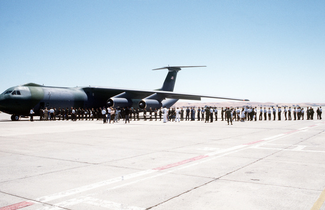 Military personnel prepare to board C-141B Starlifter aircraft after being flown to Travis from Naval Station, Subic Bay and Clark Air Force Base, Republic of the Philippines. The servicemen and women, along with dependents, were evacuated in the aftermath of Mount Pinatubo's eruption. The volcano, which erupted for the first time in over 600 years, forced the U.S. military to coordinate Operation Fiery Vigil evacuation efforts to remove more than 20,000 evacuees from the area