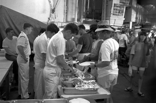 Navy personnel aboard the aircraft carrier USS MIDWAY (CV-41) serve a meal to evacuees from Clark Air Base and Naval Station, Subic Bay. Military personnel and dependents are being transported from the area in the aftermath of the eruption of Mount Pinatubo, a volcano in the Philippines that came alive on June 10th for the first time in over 600 years
