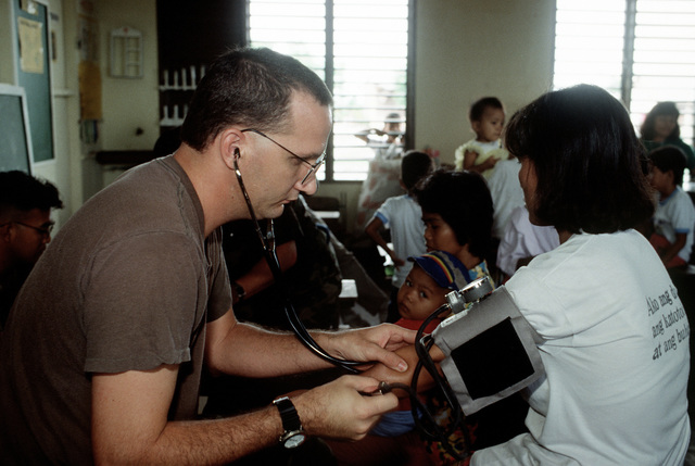 SSGT Ed Kiefer, a medical technician with the 3rd Medical Group, takes a girl's blood pressure while participating in a medical civic action program (MEDCAP) at the Santa Rosa School. The school is being used as a clinic for more than 1,300 evacuees who have fled the mudslides and flooding caused by heavy rains that fell following the eruption of Mount Pinatubo