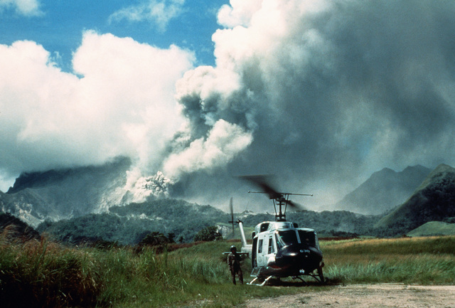 STAFF SGT. Skinowski, a helicopter flight engineer from the 3rd Tactical Fighter Wing, stands by his UH-1N Iroquois helicopter as clouds of ash pour from Mount Pinatubo in the background prior to its eruption. The volcano's activity is forcing the U.S. military to coordinate removal of over 20,000 evacuees from Clark Air Base and Naval Station, Subic Bay, during Operation Fiery Vigil