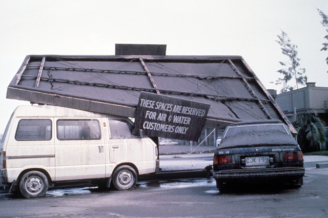 The awning of a gas station is collapsed on automobiles under the weight of the four inches of volcanic ash that fell as a result of the June 10 eruption of Mount Pinatubo. More than 20,000 evacuees have been removed from the area as a part of the U.S. miltary's Operation Fiery Vigil